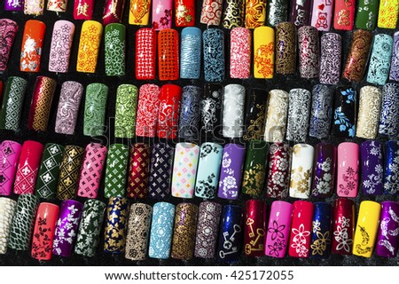 Nail samples, big collection of fingernails painted in various color with different pattern, selective focus
