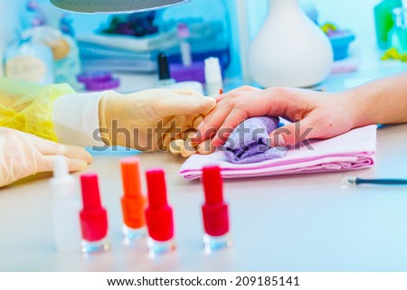Nail treatment in the beauty salon, hands and nail closeup