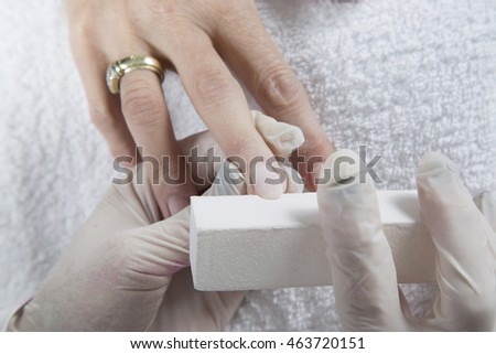 Nail Treatment - Manicurist Polishing Fingernails With Nail File, Making A Perfect Nail Form On White Towel Closeup