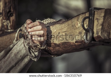 Nailed hand on wooden cross. Crucifixion of Jesus Christ. - stock photo