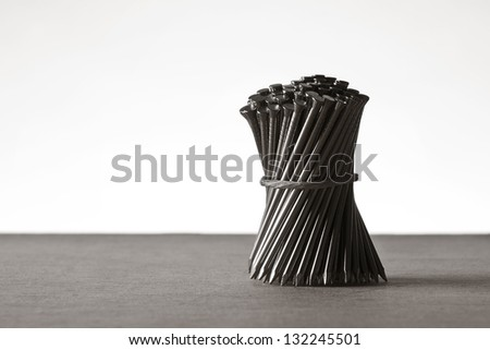 nails arrange with string tided around them into a neat bunch - stock photo