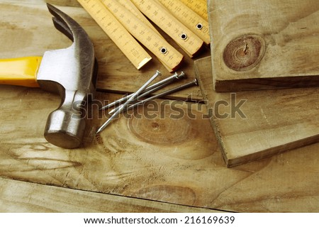Nails, hammer and folding ruler on wood - stock photo
