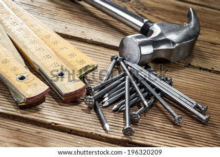 Nails, hammer and folding ruler on wooden background - stock photo