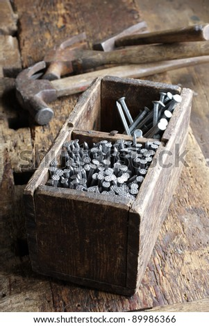 Nails in old wooden box on workbench, hammers on background