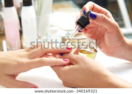 Nails top coat finishing vernis after nail polish in woman hands at salon - stock photo