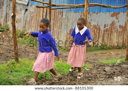 NAIROBI, KENYA- OCTOBER 13: Unidentified children walk in mud for to go school on October 13, 2011 in Nairobi, Kenya. Kibera is the largest slum in Nairobi, and the second largest urban slum in Africa - stock photo