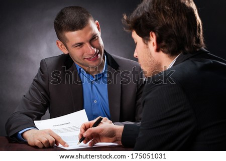 Naive man signing the usury contract with crook - stock photo