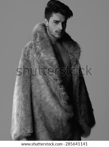Naked athlete with strong body and tattoo, with fur coat - stock photo