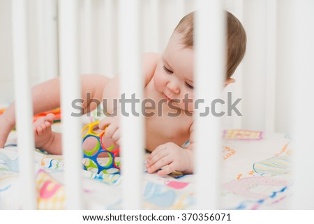 naked baby in a crib playing with a ball - stock photo