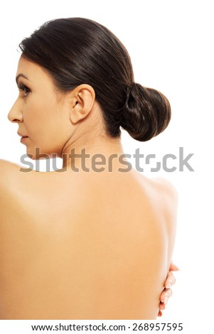 Naked back of a beautiful woman embracing herself. - stock photo