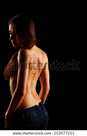 naked back of young girl with henna tattoo mehendi on dark backround
