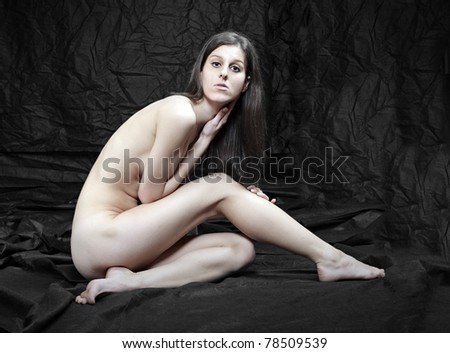 Naked beautiful woman posing on black background. - stock photo