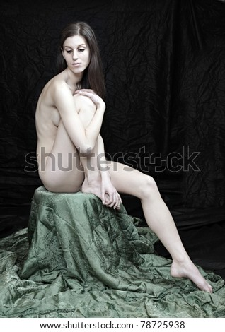 Naked beautiful woman posing on black background.