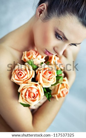 Naked beauty holding roses - stock photo