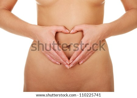 Naked belly of young woman with hands showing symbolic shape of heart. - stock photo