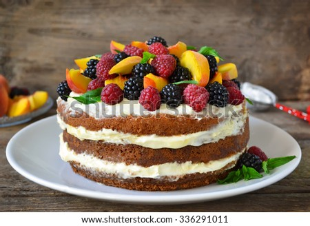 Naked cake with cream, decorated with raspberries, blackberries, peaches  - stock photo