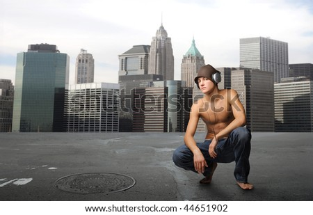 naked chest boy listening music in a city street - stock photo