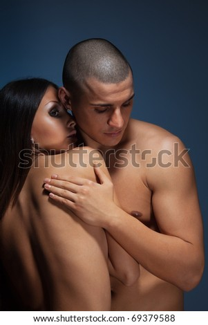 Naked couple with man snuggle up girlfriend on dark background