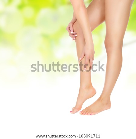 naked female legs being massaged with hands over green - stock photo