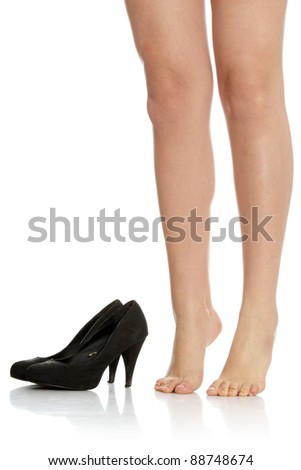 Naked female legs next to high heels, isolated on white