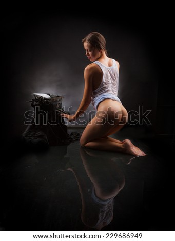 Naked girl in a white shirt sitting in the water next to the typewriter on a black background. - stock photo