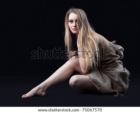 naked girl in hessian sit in dark - stock photo