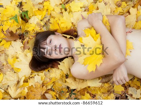 Naked girl lies in maple leaves at autumn park - stock photo