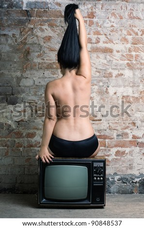 Naked girl shows her long hair, sitting with his back to the viewer on a retro TV.