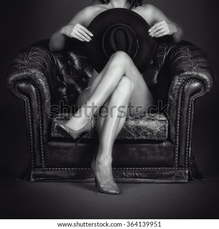 Naked girl sitting in the armchair - stock photo