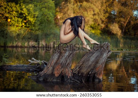 Naked girl sitting on a snag in the middle of the lake showing her beautiful body. - stock photo