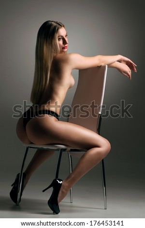 Naked girl with long hair sitting backwards on a chair in his underwear - stock photo