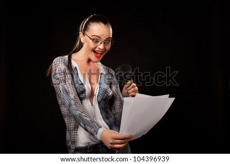 Naked happy shocked woman covered with body paint business suit, holding a magnyfing glass on documents.Concept image of sexual issues at work. High resolution studio picture on black background. - stock photo