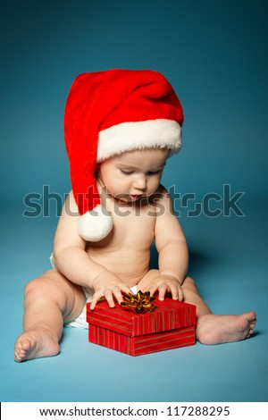 naked little boy in diapers with hat of Santa Claus - stock photo