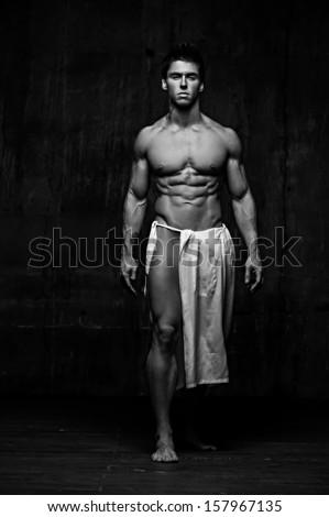 Naked male model against black background - stock photo