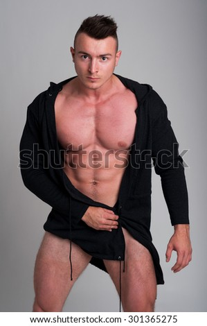 Naked male model posing in studio wearing a black hoodie - stock photo