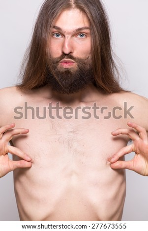 Naked man jokingly play with his nipples - stock photo