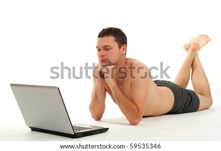 naked man lying on the  floor and working on laptop - stock photo