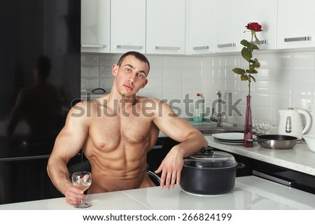 Naked man resting in the kitchen with his hand on the pan. - stock photo
