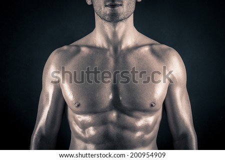 Naked man torso against black background.