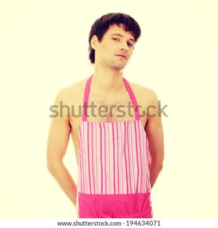 Naked man wering pink apron. - stock photo