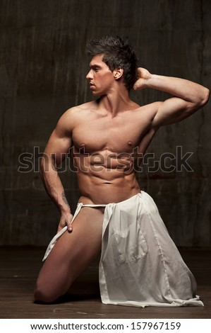 Naked man with loincloth on his knees - stock photo