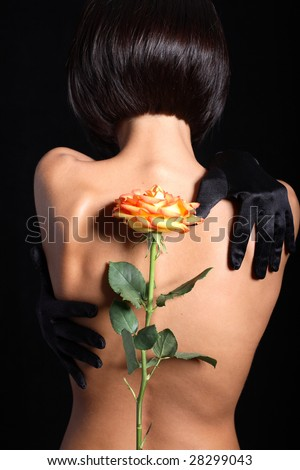 Naked model touching back with arms. Rose in front of her - stock photo