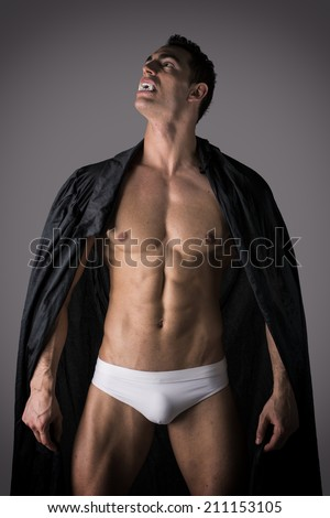 Naked muscular fit young man in briefs posing as a vampire or Dracula in a black cloak showing off his powerful body raising his head to the sky bearing his fangs - stock photo