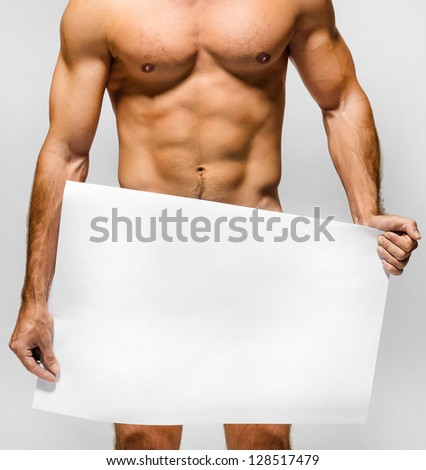 Naked muscular man covering with a banner  (copy space) isolated on white - stock photo