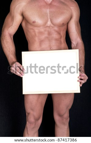 Naked muscular man covering with a box (copy space) - stock photo