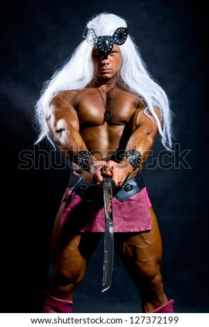 Naked muscular man warrior with a sword. Against a dark background