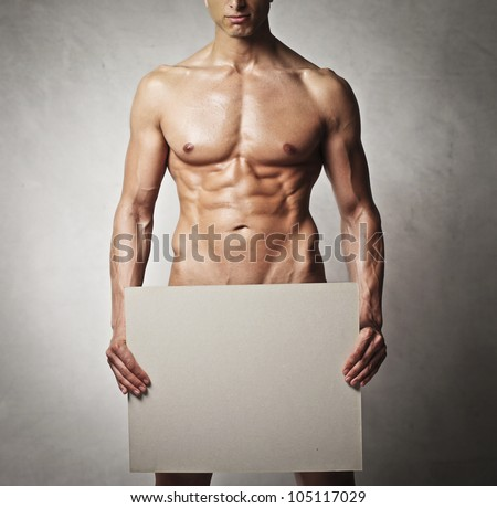 Naked muscular young man with a white billboard covering his waist