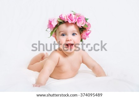 Naked newborn baby with a wreath of flowers