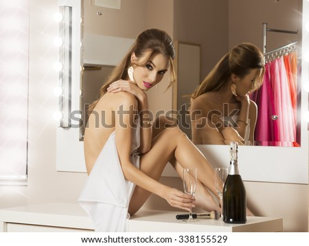 naked pretty girl in dressing room sitting near mirror with white towel on her body, bottle of champagne and make-up brush. preparing for the new year night party  - stock photo
