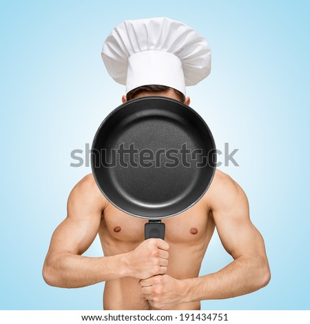 Naked restaurant chef hiding behind a frying pan for a menu with prices. - stock photo